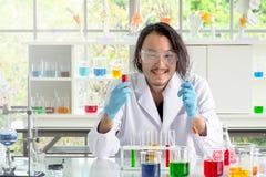 Hombre asiático del químico que comprueba la sustancia líquida en tubos de ensayo imagenes de archivo
