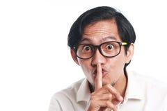Hombre asiático divertido que hace callar gesto imagen de archivo libre de regalías