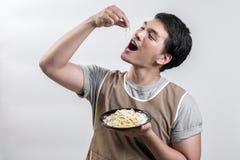 Hombre asiático en delantal con carbonara de los espaguetis fotografía de archivo