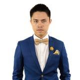 Hombre asiático en el bowtie azul del traje, broche Fotografía de archivo