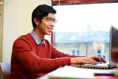 Hombre asiático en el funcionamiento de vidrios en el ordenador portátil Fotos de archivo libres de regalías