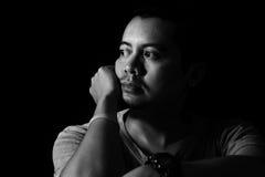 Hombre asiático en la oscuridad que mira hacia fuera la ventana Fotos de archivo libres de regalías