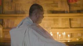 Hombre asiático en templo auténtico mientras que ritual de la religión en fondo ardiendo de la vela Esperanza feliz del hombre en metrajes