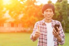 Hombre asiático feliz con noticias o el mensaje del teléfono elegante en jardín, Fotos de archivo