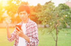 Hombre asiático feliz con noticias o el mensaje del teléfono elegante en jardín, Imagenes de archivo