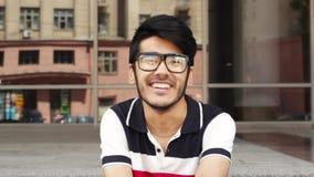 Hombre asiático feliz en vidrios que sonríe a la cámara metrajes
