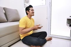Hombre asiático feliz que lleva a cabo el gamepad y que juega a los videojuegos Fotografía de archivo libre de regalías