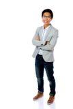 Hombre asiático feliz que se coloca con los brazos doblados Imagen de archivo libre de regalías