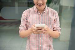 Hombre asiático feliz que sonríe como él lee salidas derechas de un mensaje de texto Imagen de archivo libre de regalías