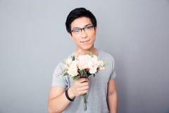 Hombre asiático feliz que sostiene las flores Imagenes de archivo