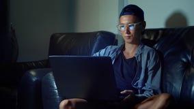 Hombre asiático hermoso joven en vidrios con reflexiones usando su ordenador portátil, sentándose por la tarde en el cuarto En la metrajes