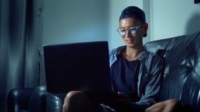 Hombre asiático hermoso joven en vidrios con reflexiones usando su ordenador portátil, sentándose por la tarde en el cuarto En la almacen de video