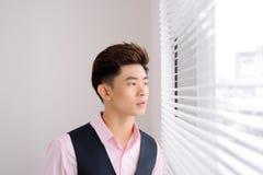 Hombre asiático hermoso que hace una pausa la ventana Fotos de archivo