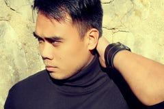 Hombre asiático hermoso que lleva a cabo su cabeza Imagen de archivo