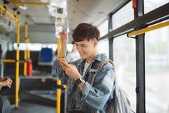 Hombre asiático hermoso que se sienta en autobús de la ciudad y que mecanografía un mensaje en t imagenes de archivo