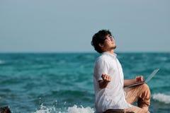 Hombre asiático joven acertado con el ordenador portátil que celebra la libertad Foto de archivo