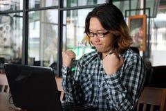 Hombre asiático joven acertado del inconformista que aumenta las manos en el lugar de trabajo de la oficina Foto de archivo libre de regalías