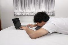 Hombre asiático joven cansado que trabaja con el ordenador portátil en la cama Imágenes de archivo libres de regalías