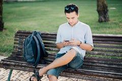 Hombre asiático joven casual que usa el teléfono elegante que se sienta en banco en el CIT Imagenes de archivo