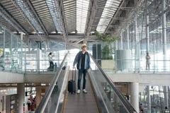 Hombre asiático joven con equipaje abajo de la escalera móvil en aeropuerto Fotos de archivo