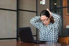 Hombre asiático joven con exceso de trabajo cansado que estira después de trabajo difícilmente con el ordenador portátil en ofici Foto de archivo