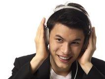 Hombre asiático joven con los auriculares Imagenes de archivo