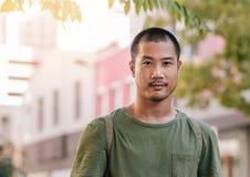 Hombre asiático joven confiado que se coloca en una calle de la ciudad imágenes de archivo libres de regalías