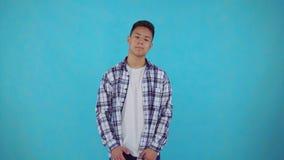 Hombre asiático joven confuso en fondo azul metrajes