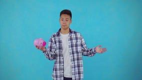 Hombre asiático joven confuso que sostiene una hucha en fondo azul metrajes