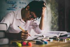 Hombre asiático joven del estudiante que se sienta en el escritorio en estudiar y rea del hogar Foto de archivo