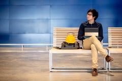 Hombre asiático joven del ingeniero que se sienta con el casco de seguridad y la tableta Fotografía de archivo