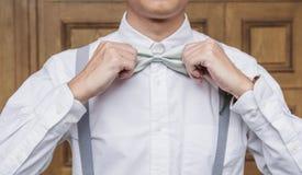 Hombre asiático joven del primer en la camisa blanca que lleva a cabo la corbata de lazo fotos de archivo
