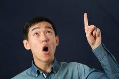 Hombre asiático joven divertido que destaca su dedo índice Imagen de archivo libre de regalías