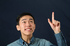 Hombre asiático joven divertido que destaca su dedo índice Imágenes de archivo libres de regalías