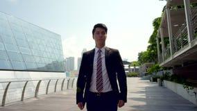 Hombre asiático joven en el traje de negocios que camina con confianza al aire libre en la cámara lenta almacen de metraje de vídeo