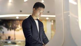 Hombre asiático joven en la chaqueta y la camisa que buscan para la información en quiosco wayfinding interactivo almacen de metraje de vídeo