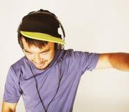 Hombre asiático joven en música que escucha del sombrero y de los auriculares en b blanco Imagenes de archivo