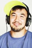 Hombre asiático joven en música que escucha del sombrero y de los auriculares en b blanco Fotografía de archivo
