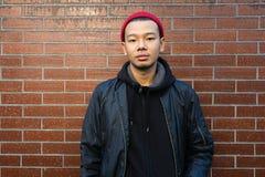 Hombre asiático joven hermoso Chaqueta negra que lleva y gorrita tejida roja Lo Foto de archivo libre de regalías