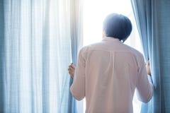Hombre asiático joven que abre la cortina azul en sala de estar fotografía de archivo