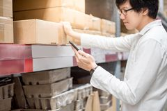 Hombre asiático joven que comprueba la lista de compras del smartphone en wareho foto de archivo libre de regalías