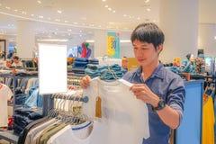 Hombre asiático joven que elige la camiseta en tienda de ropa en el centro comercial, mirando las camisetas blancas del color, fotos de archivo