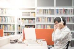 Hombre asiático joven que escucha la música en biblioteca Imagen de archivo
