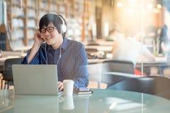 Hombre asiático joven que escucha la música en biblioteca Foto de archivo
