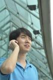 Hombre asiático joven que habla en el teléfono celular Imágenes de archivo libres de regalías