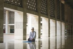 Hombre asiático joven que hace Salat en la mezquita fotografía de archivo