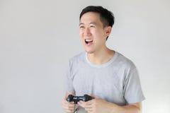 Hombre asiático joven que juega a los videojuegos Imagenes de archivo