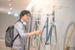 Hombre asiático joven que mira la bicicleta en tienda de la bici Imágenes de archivo libres de regalías