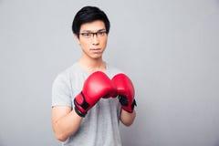 Hombre asiático joven que se coloca en guantes de boxeo Fotografía de archivo libre de regalías