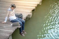 Hombre asiático joven que se sienta en el puente que escucha la música Fotografía de archivo libre de regalías